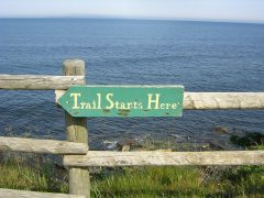 trail starts here sign above the ocean
